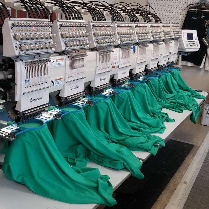 Custom embroidery printed on green shirts using machine
